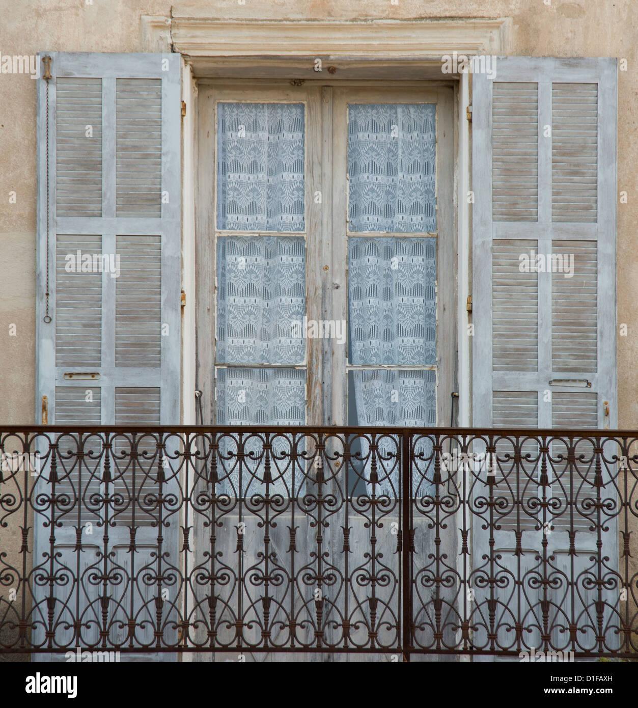 Una vieja ventana, balcón y cortinas en el pintoresco pueblo de Aregno en el interior de la región de Imagen De Stock