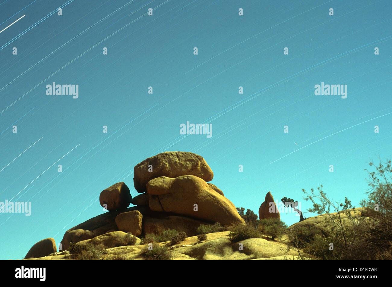 El tiempo de exposición de las estrellas con formaciones de roca en el primer plano, el Parque Nacional Joshua Imagen De Stock