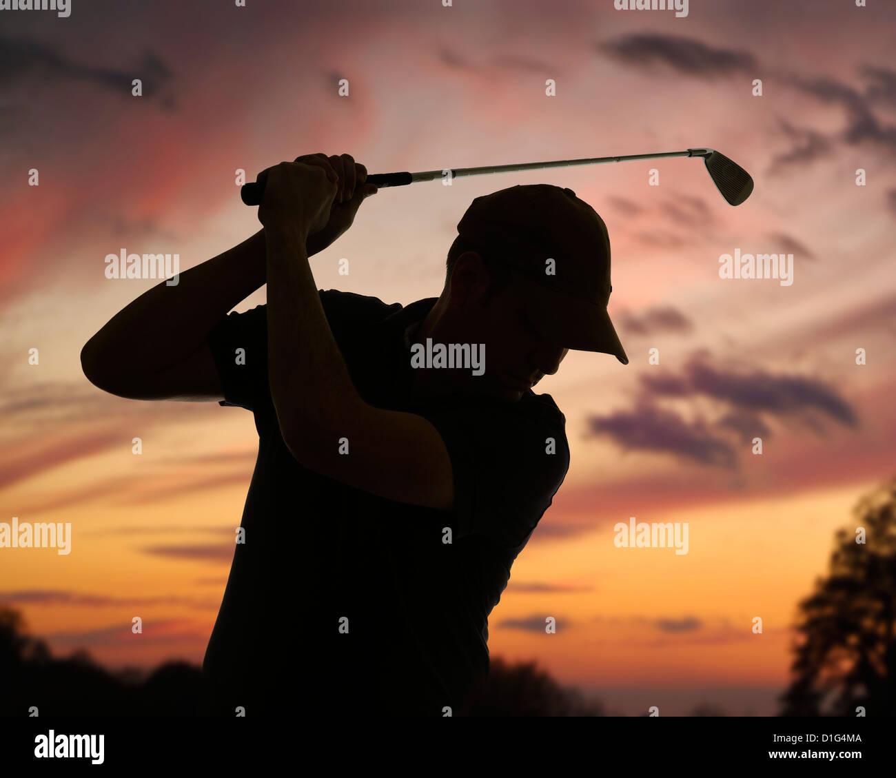 Golfista pegándole a una pelota de golf siluetas contra un cielo del anochecer. Cerca. Imagen De Stock