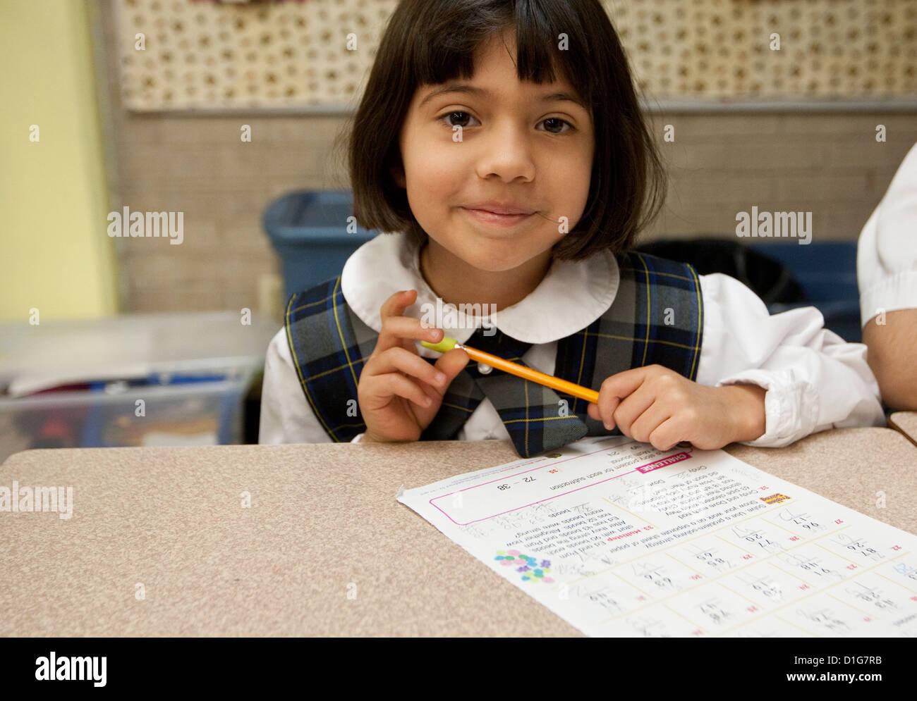 Hispano sonriente niña de segundo grado de la escuela primaria en uniforme  en el aula en la escuela católica privada en Texas 3d8e4c8a151