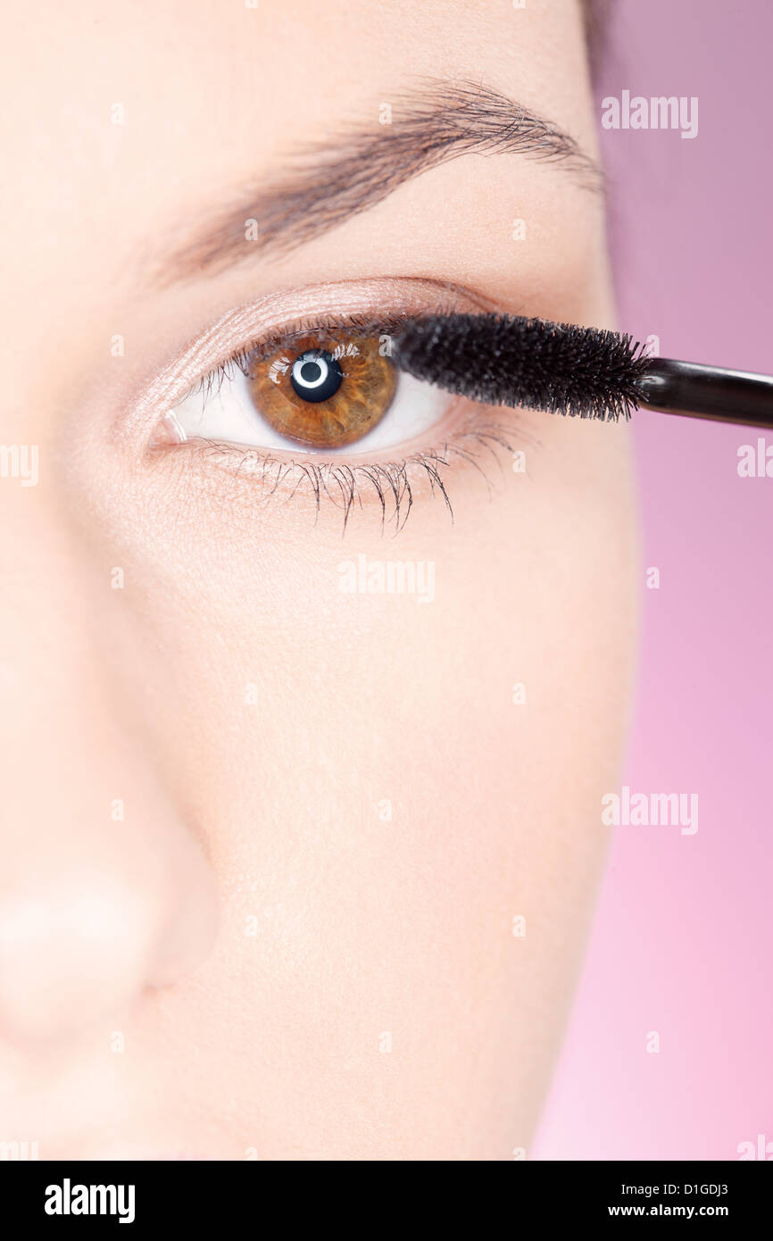 Cerca de una mujer de aplicar el rímel en el ojo Imagen De Stock