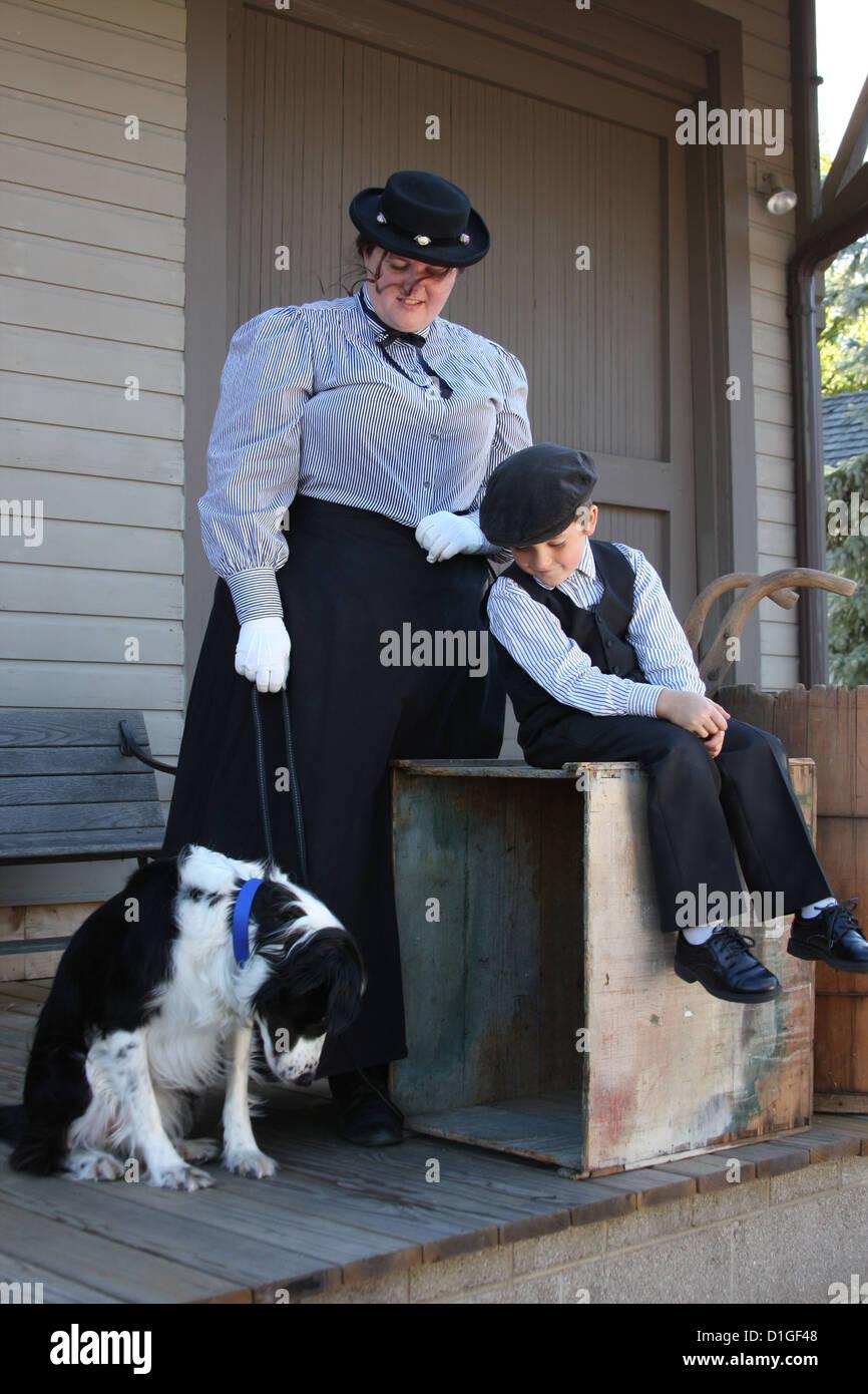 Una mujer, perro y niño esperando en un train depot platform Foto de stock