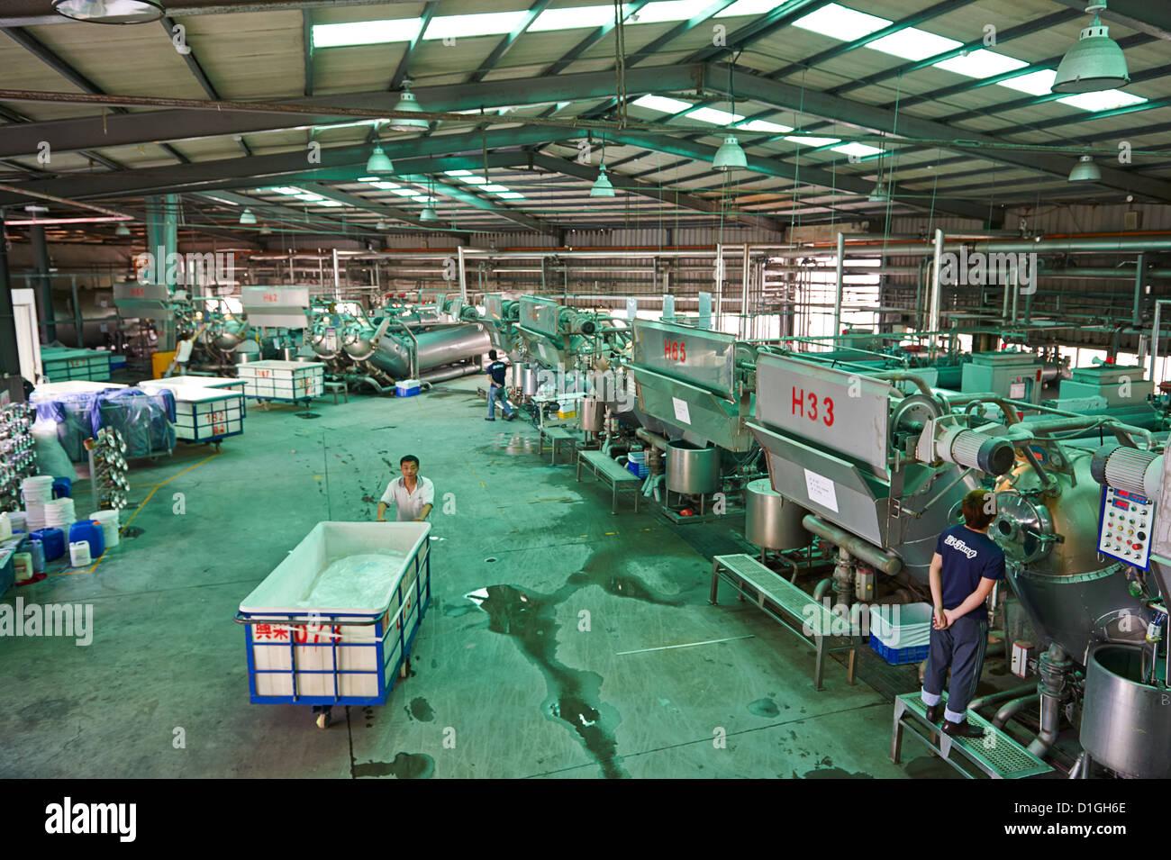 En el interior de una fábrica de tejidos y textiles, aquí un trabajador empuja una bandeja gigante junto Imagen De Stock