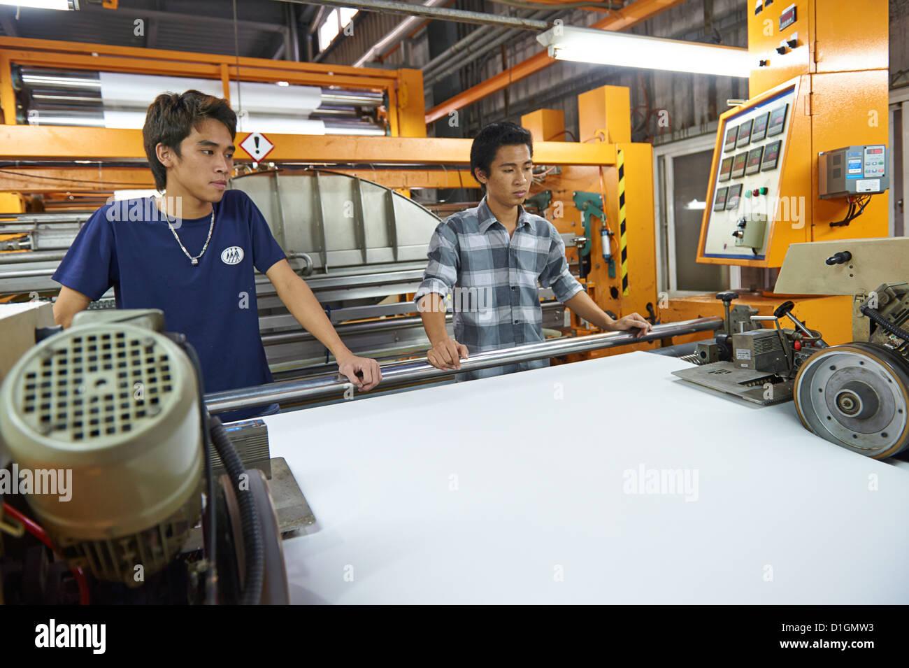 Los jóvenes trabajadores de la fábrica textil tejido recién prensados de inspección Imagen De Stock