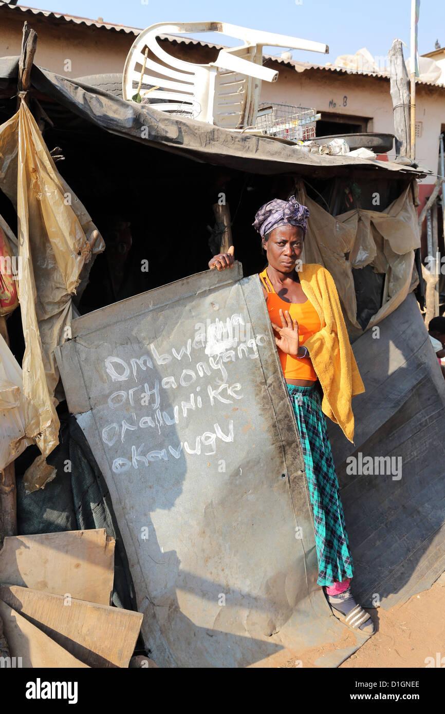 Una mujer se encuentra en el umbral de su choza en un campamento de un barrio pobre en Tsumeb, Namibia Imagen De Stock