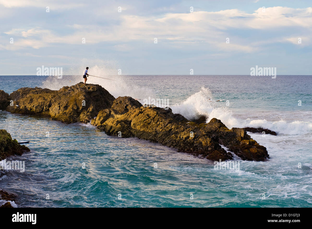 Pescador siendo golpeado por una ola, mientras rock pesca en Snapper Rocks, Tweed Heads, Gold Coast, Queensland, Imagen De Stock