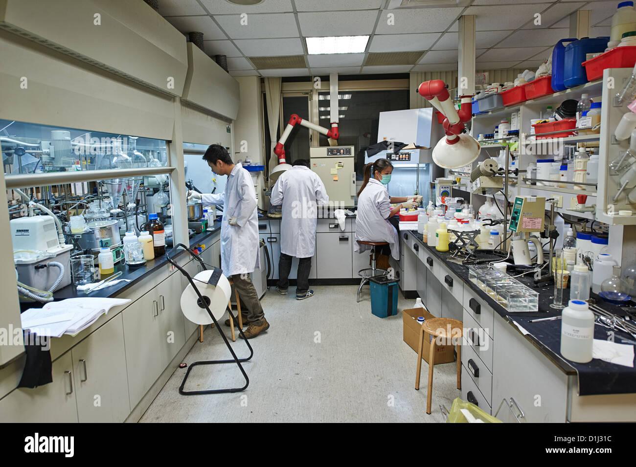 Los trabajadores de laboratorio investigando ingredientes y productos químicos en la industria textil y la Imagen De Stock
