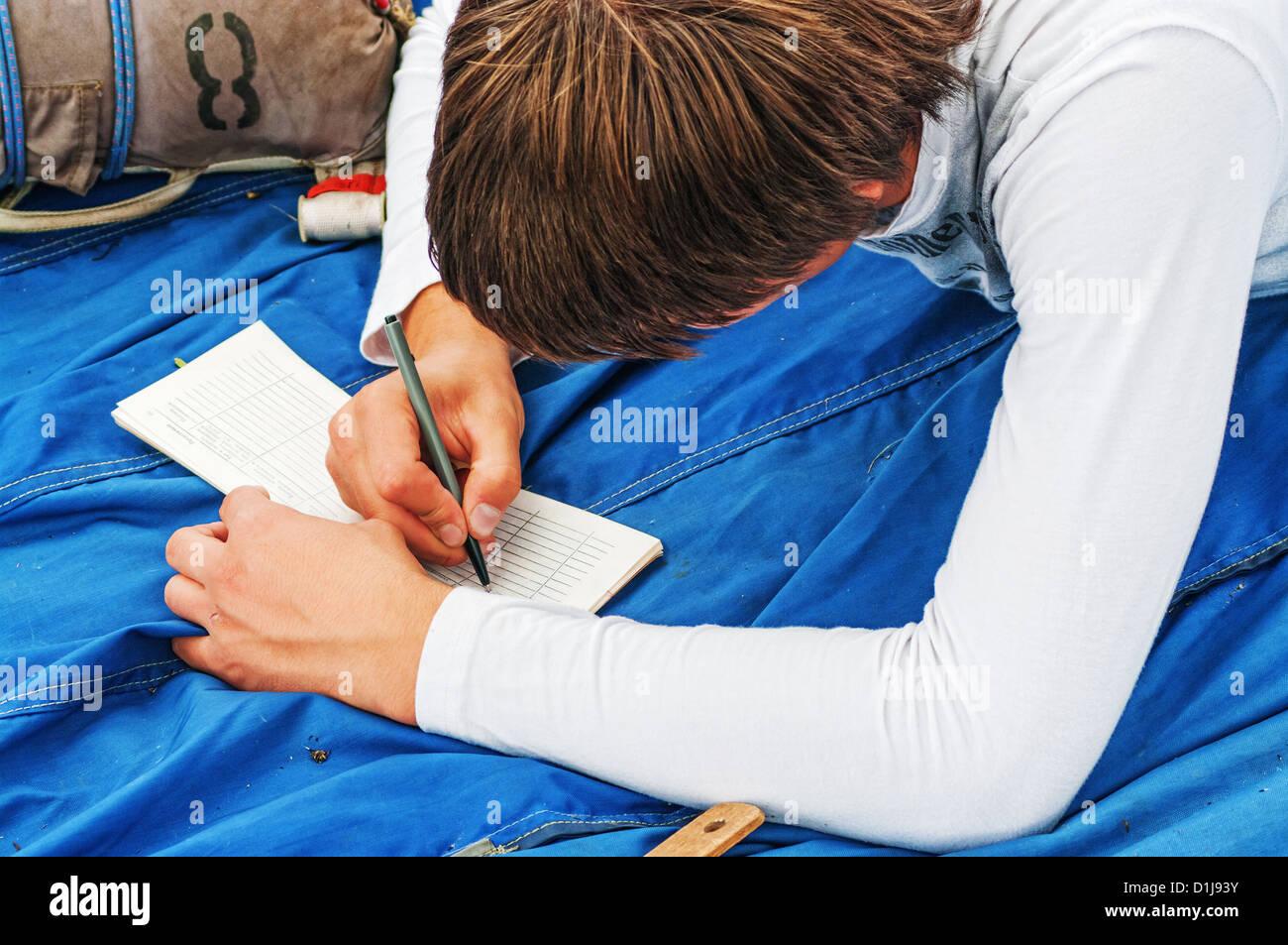 El chico paracaidista escribe en el pasaporte de la parachut. Foto de stock