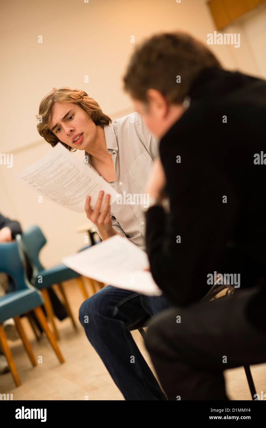 Dos actores aficionados en un 'script' en mano ensayaba lectura del nuevo teatro taller de escritura, REINO Imagen De Stock