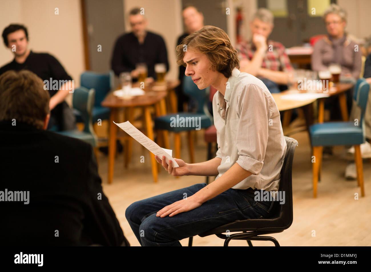 Actores aficionados en un 'script' en mano ensayaba lectura del nuevo teatro taller de escritura, REINO Imagen De Stock