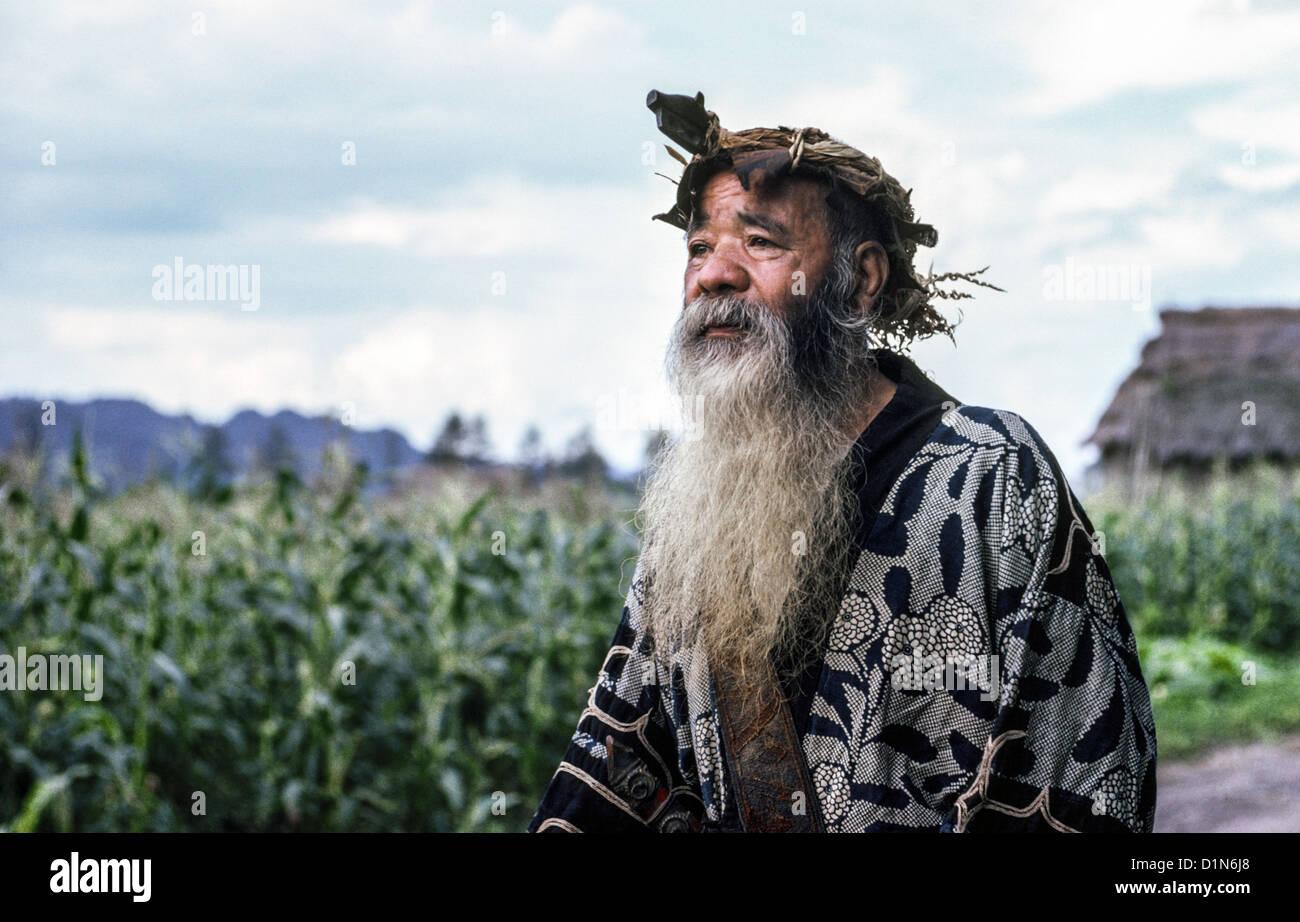 Un anciano Ainu hombre con una larga barba y vestido con traje tradicional plantea fuera de su hogar rural en Hokkaido, Imagen De Stock
