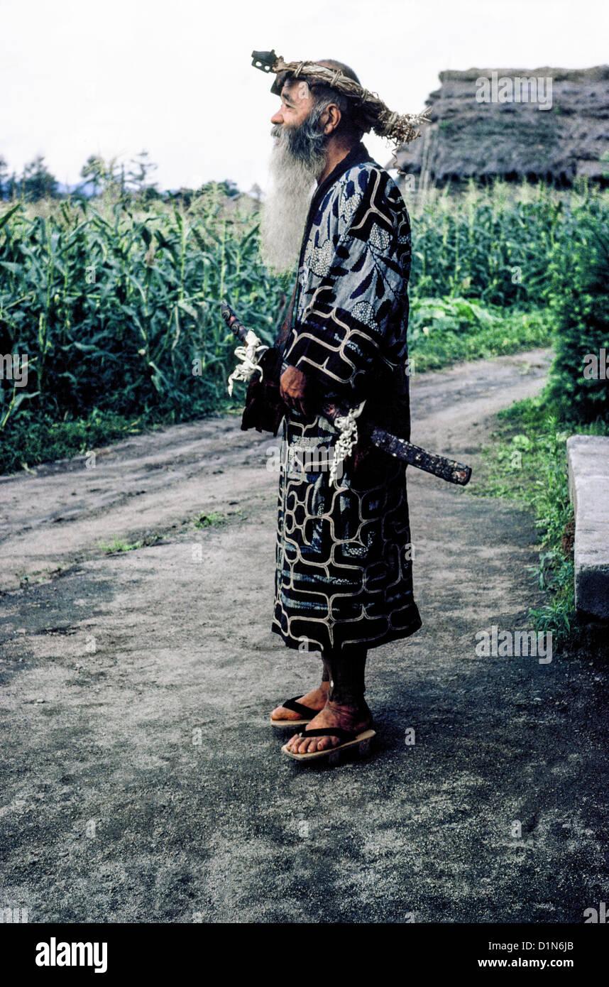 Un anciano barbudo hombre Ainu en traje tradicional y sosteniendo su espada ceremonial plantea fuera de su hogar Imagen De Stock