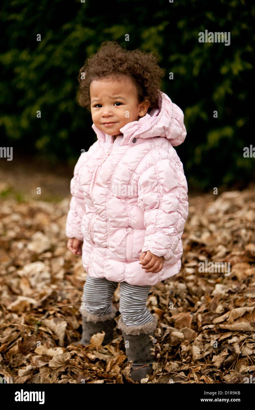 Linda niña niño jugando en hojas caídas Foto de stock