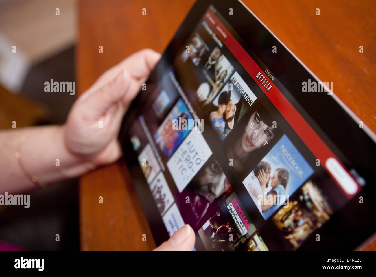 Una mujer usa la aplicación Netflix en el iPad 4. Netflix, Inc. es un proveedor estadounidense de Internet Imagen De Stock