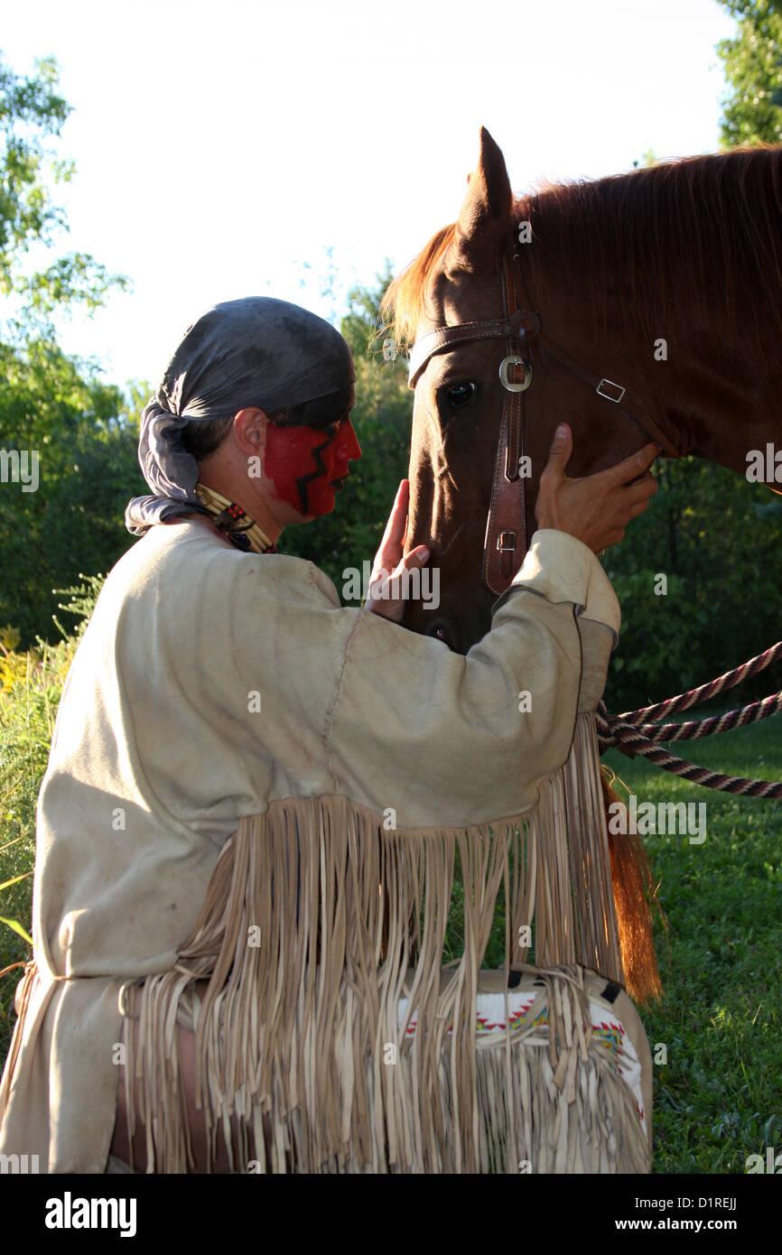 Un hombre de origen indio americano nativo con pintura facial roja  saludando a su caballo. 52f39ee6b931