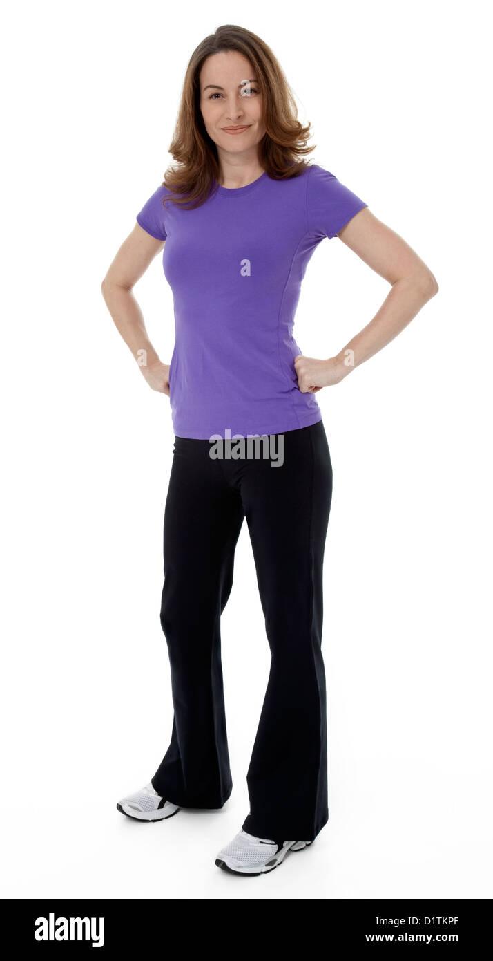52583b670 Mujer vestida en ropa deportiva con las manos en las caderas, de pie sobre  un fondo blanco.