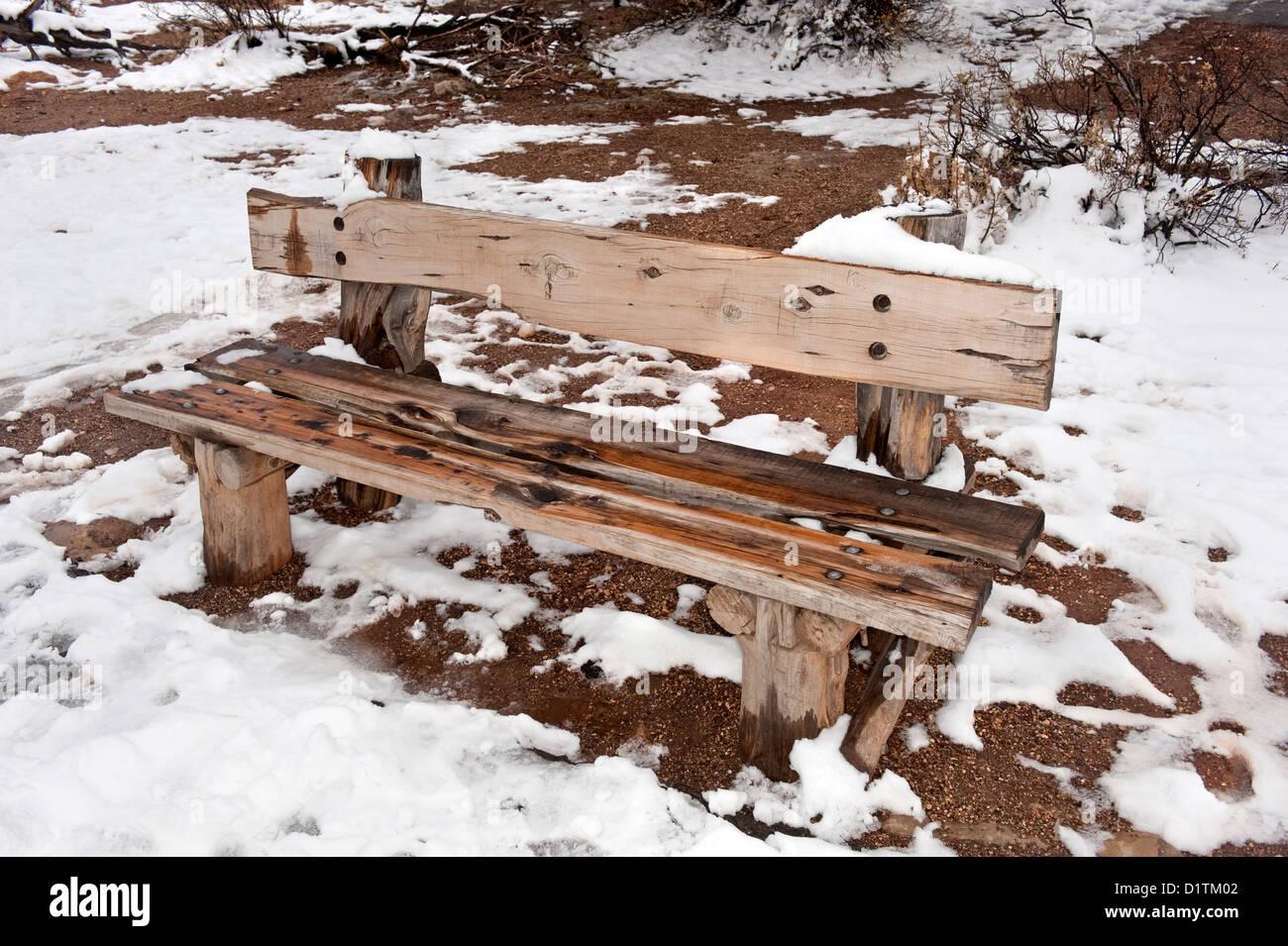 Una húmeda y fría en un banco de un parque de madera durante un día nevado Winder. Foto de stock