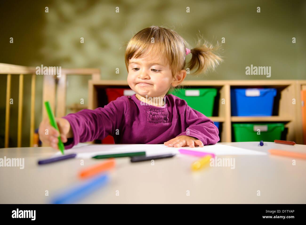 Niña divirtiéndose en la escuela y el dibujo con colores en kindergarten. Imagen De Stock