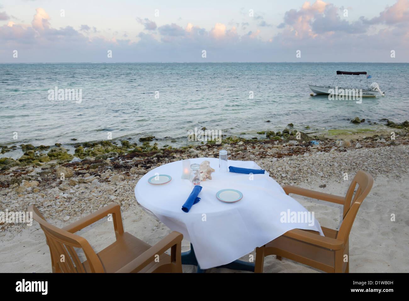 Mesa de restaurante en la playa durante la puesta de sol sobre el Caribe, extremo este de Gran Caimán. Imagen De Stock