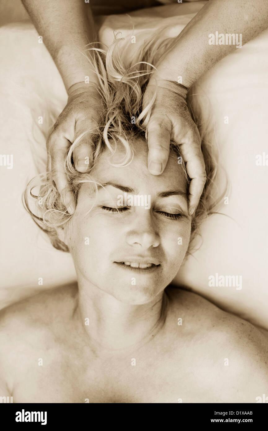 Manos de un terapista de masaje suavemente con el movimiento sacro craneal de su cliente. Imagen De Stock