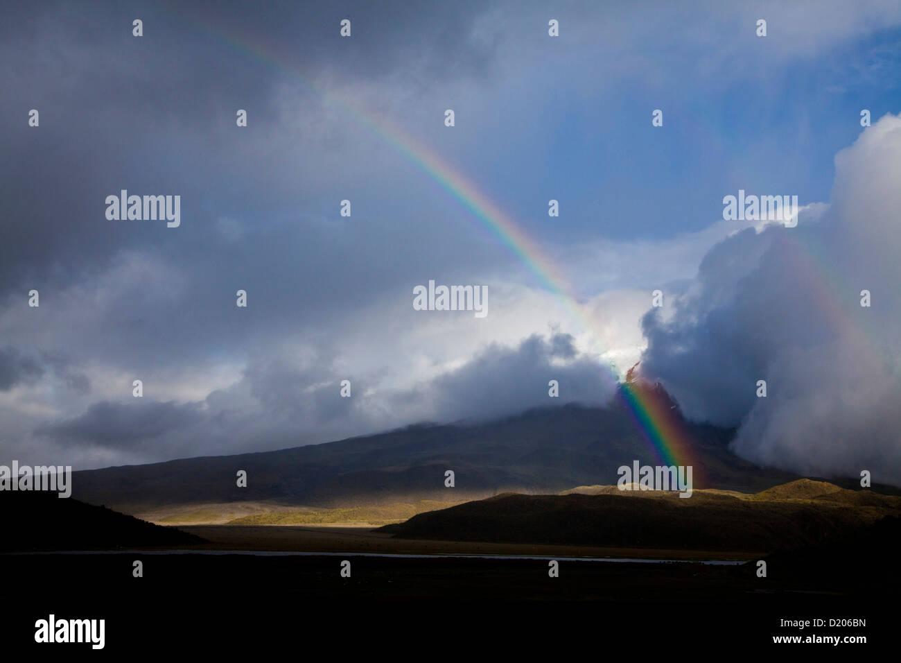 Niebla, nubes y arco iris, el Cotopaxi (con 5897 m), en el primer plano: la laguna de Limpiopungo, Andes, Ecuador, Foto de stock