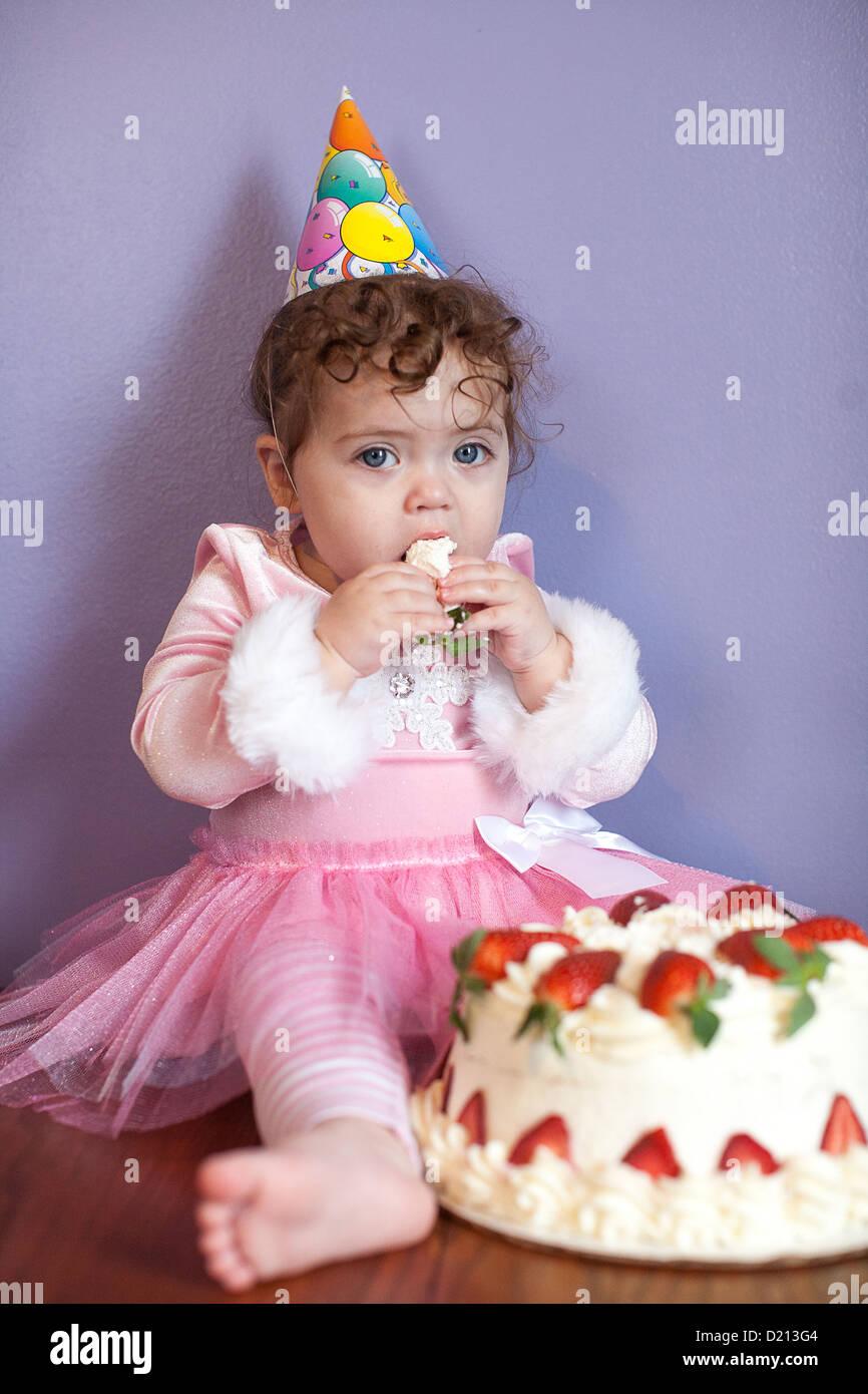 Lindo bebé niña llevando un gorro de fiesta, comiendo y jugando con ...
