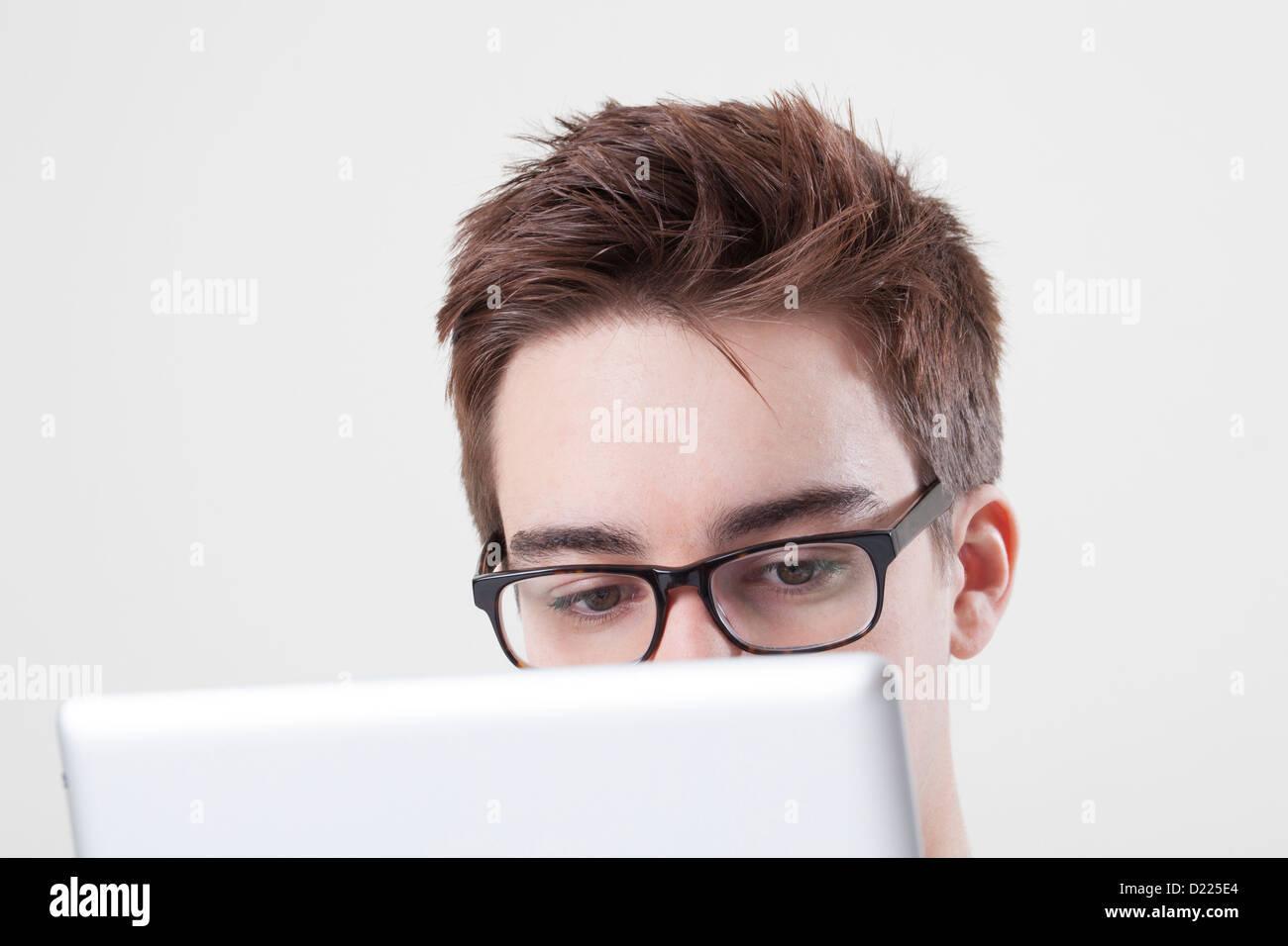 Macho joven con gafas mirando la pantalla de su ordenador portátil o tablet digital. Cerca de los ojos. Imagen De Stock