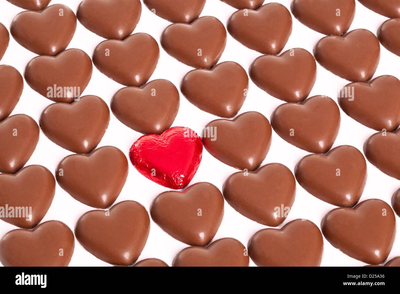 Filas de los corazones de chocolate con un extraño aún en su envoltura de papel aluminio rojo, fondo blanco. Imagen De Stock