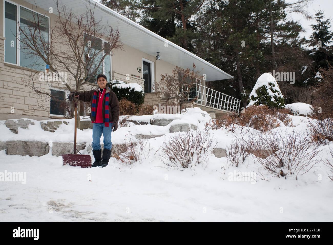 Un joven hombre de la India Oriental palas de nieve fuera de su casa Imagen De Stock