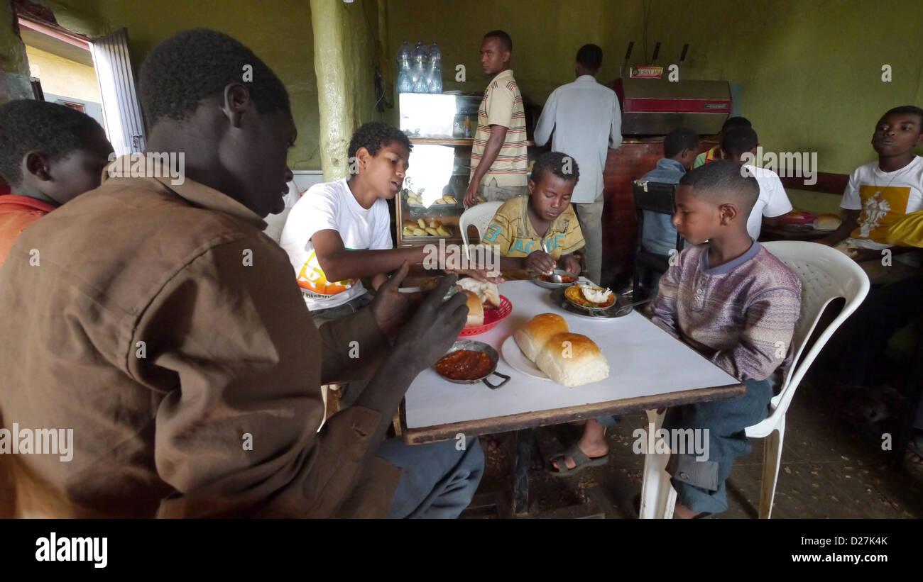 Etiopía El 'Alam Cafe' en Chagni, Beni Shangul Gumuz región. El hecho de que los niños tienen el desayuno de frijoles. Foto de stock