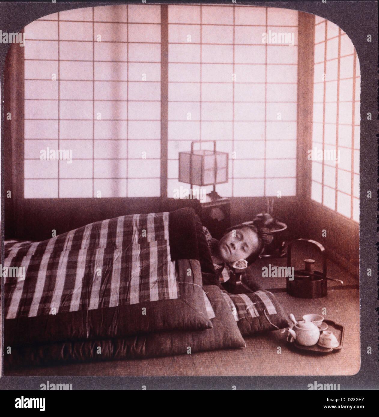 Mujer joven durmiendo entre los futones, Stereo Fotografía, 1904 Foto de stock