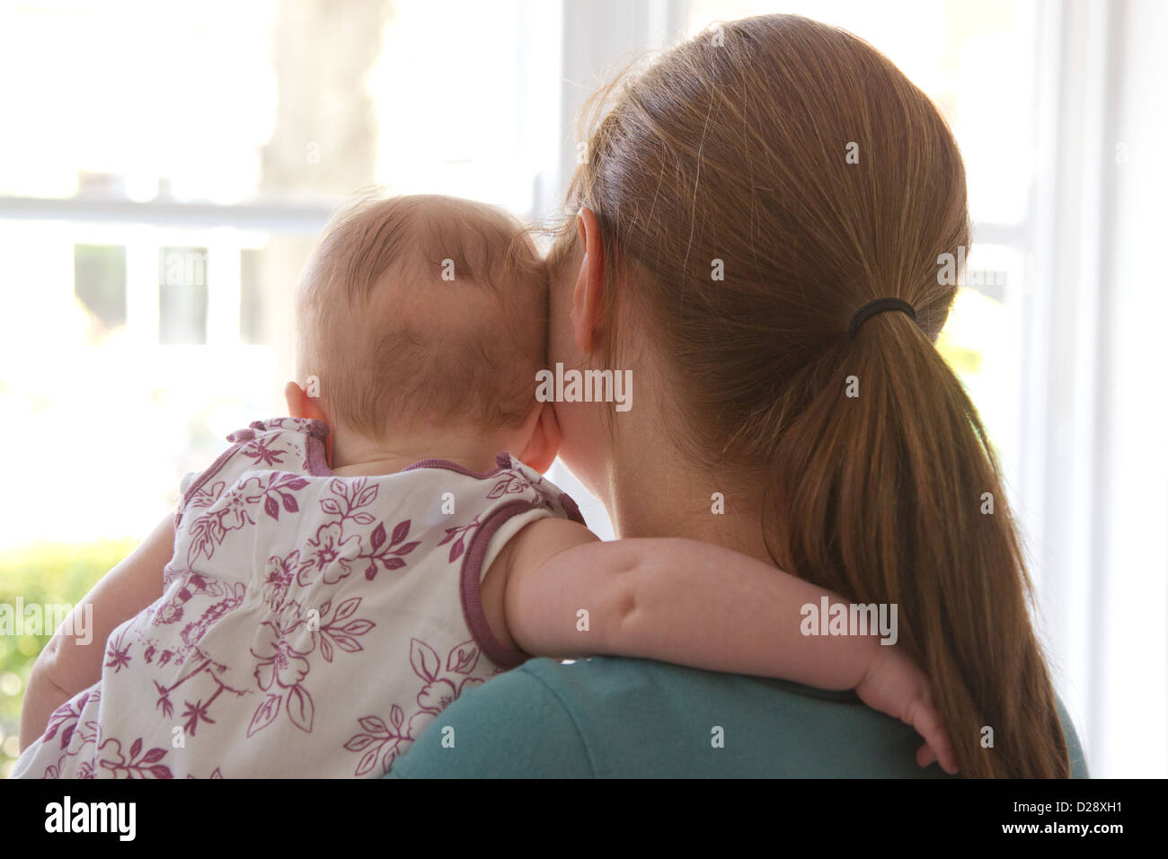 Madre y bebé mirando hacia afuera de la ventana Foto de stock