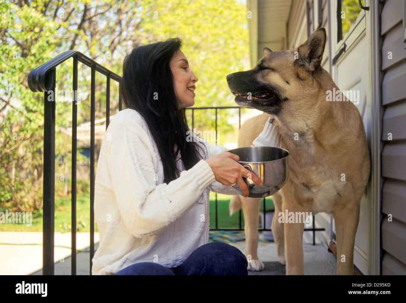 La mujer en su 30S mirando a su perro, mientras le ofrece el agua Imagen De Stock