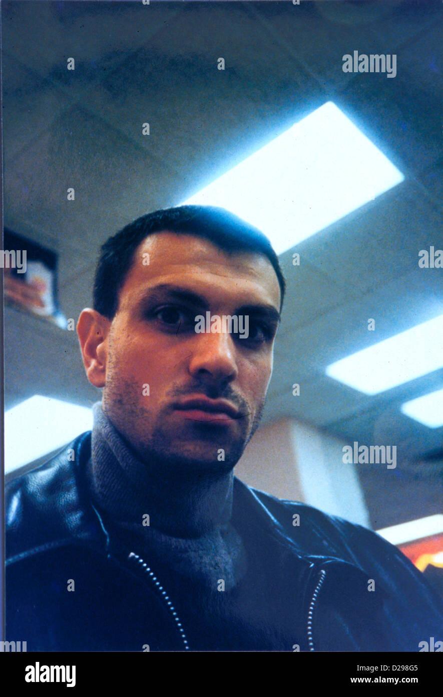 El hombre en su 30'S con cabello oscuro y chaqueta de cuero negro, en serio. Imagen De Stock