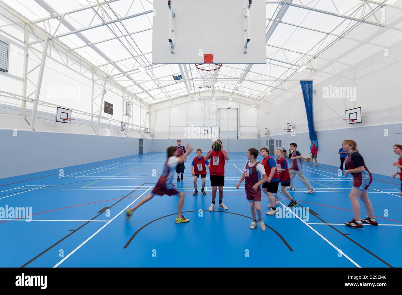 Niños jugando baloncesto en la escuela sala de deportes Imagen De Stock