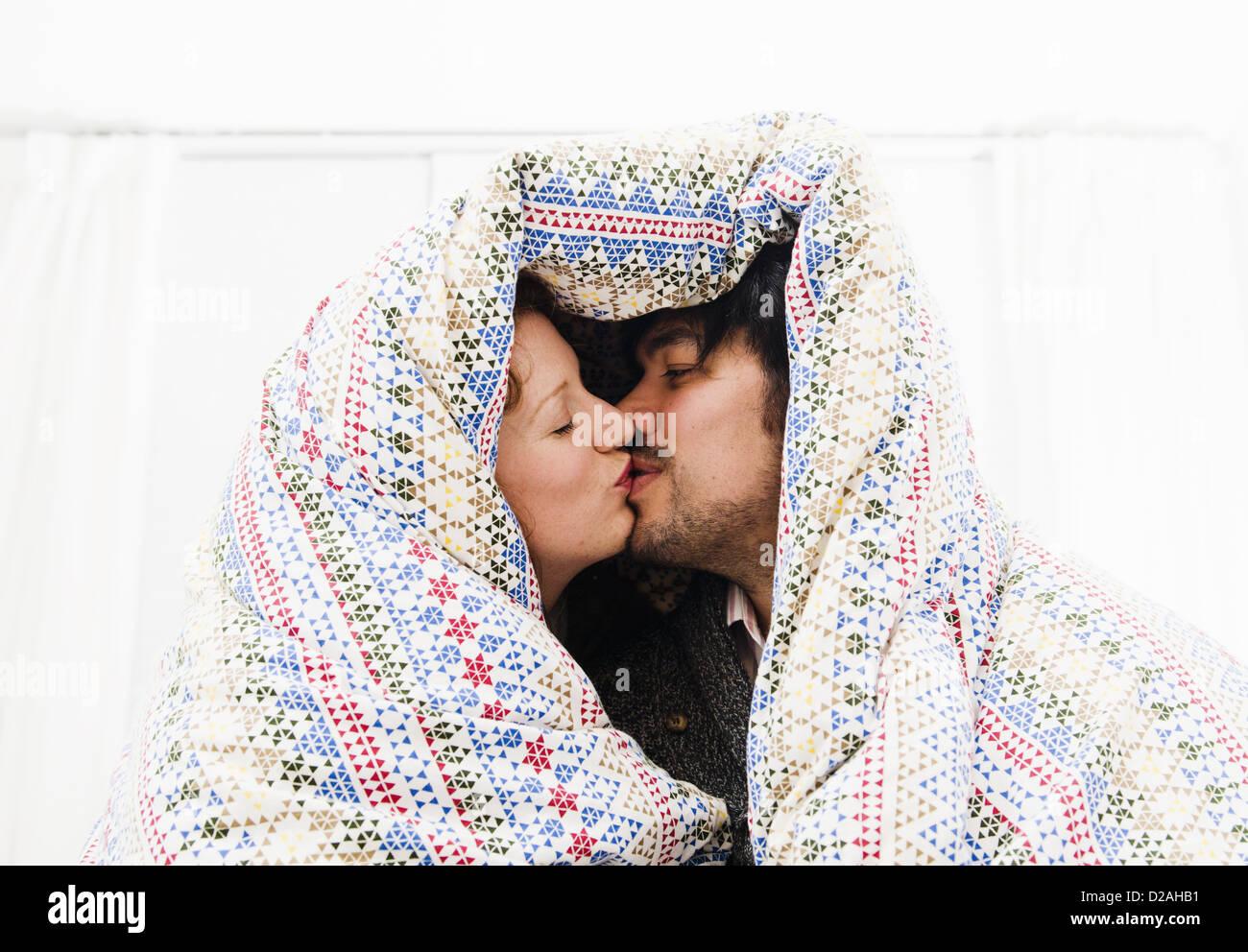 Pareja besándose bajo el edredón manta Imagen De Stock