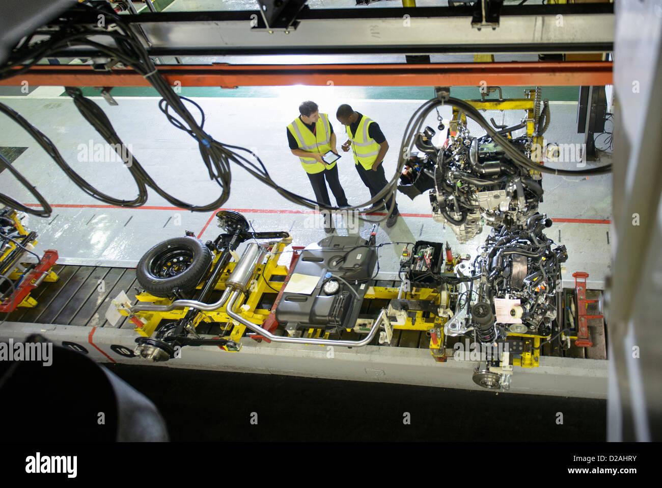 Los trabajadores hablando en fábrica de automóviles Imagen De Stock