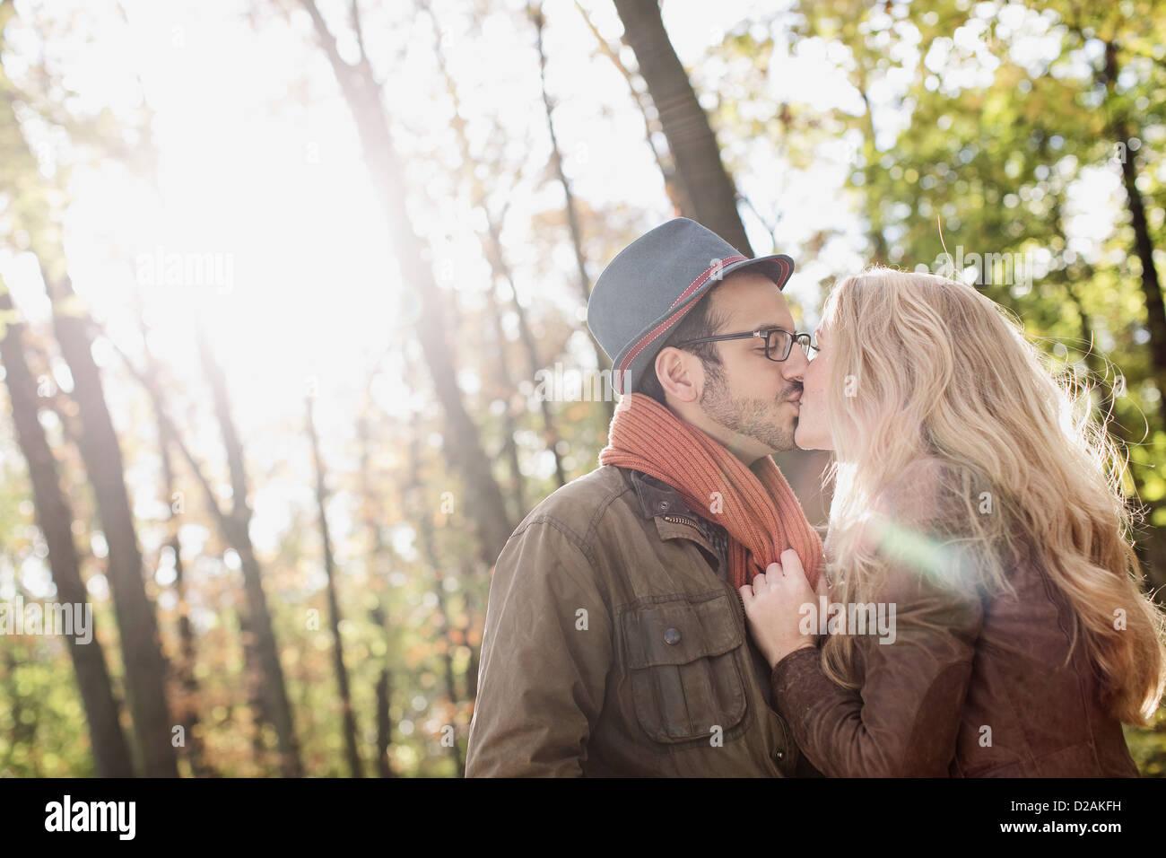 Sonriente pareja besándose en el bosque Imagen De Stock