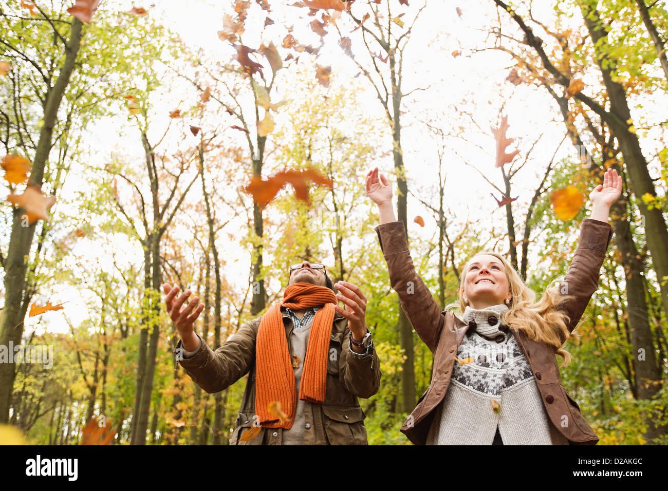Pareja sonriente jugando en hojas de otoño Foto de stock
