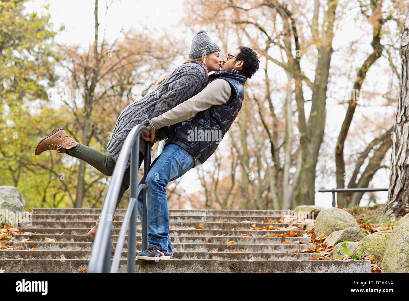 Pareja besándose sobre la baranda del parque Imagen De Stock