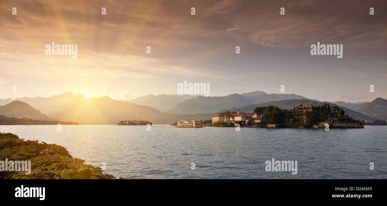Sol asciende sobre aldea rural y lago Foto de stock