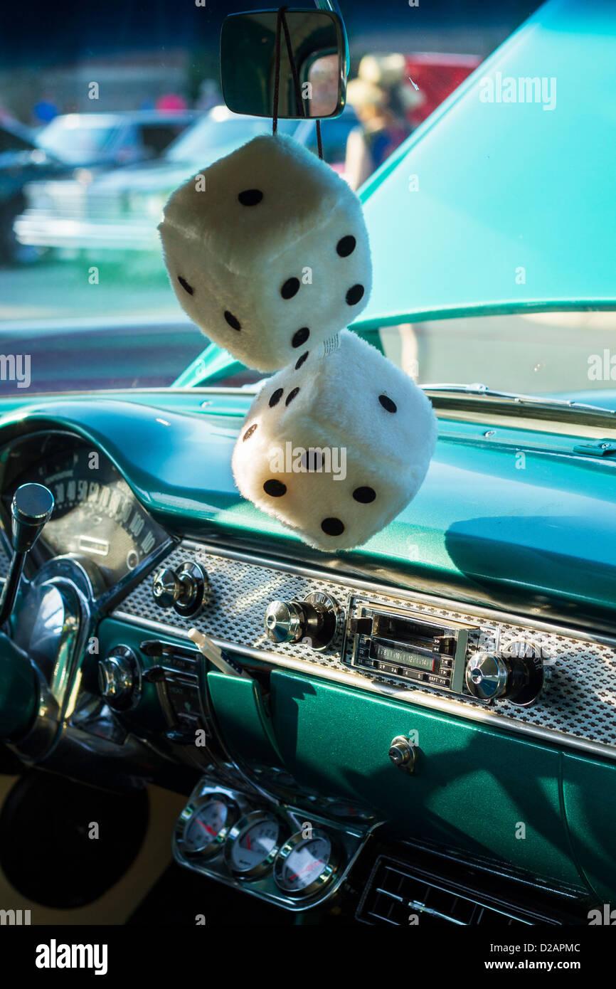 Fuzzy dados colgando del espejo de un coche clásico Imagen De Stock