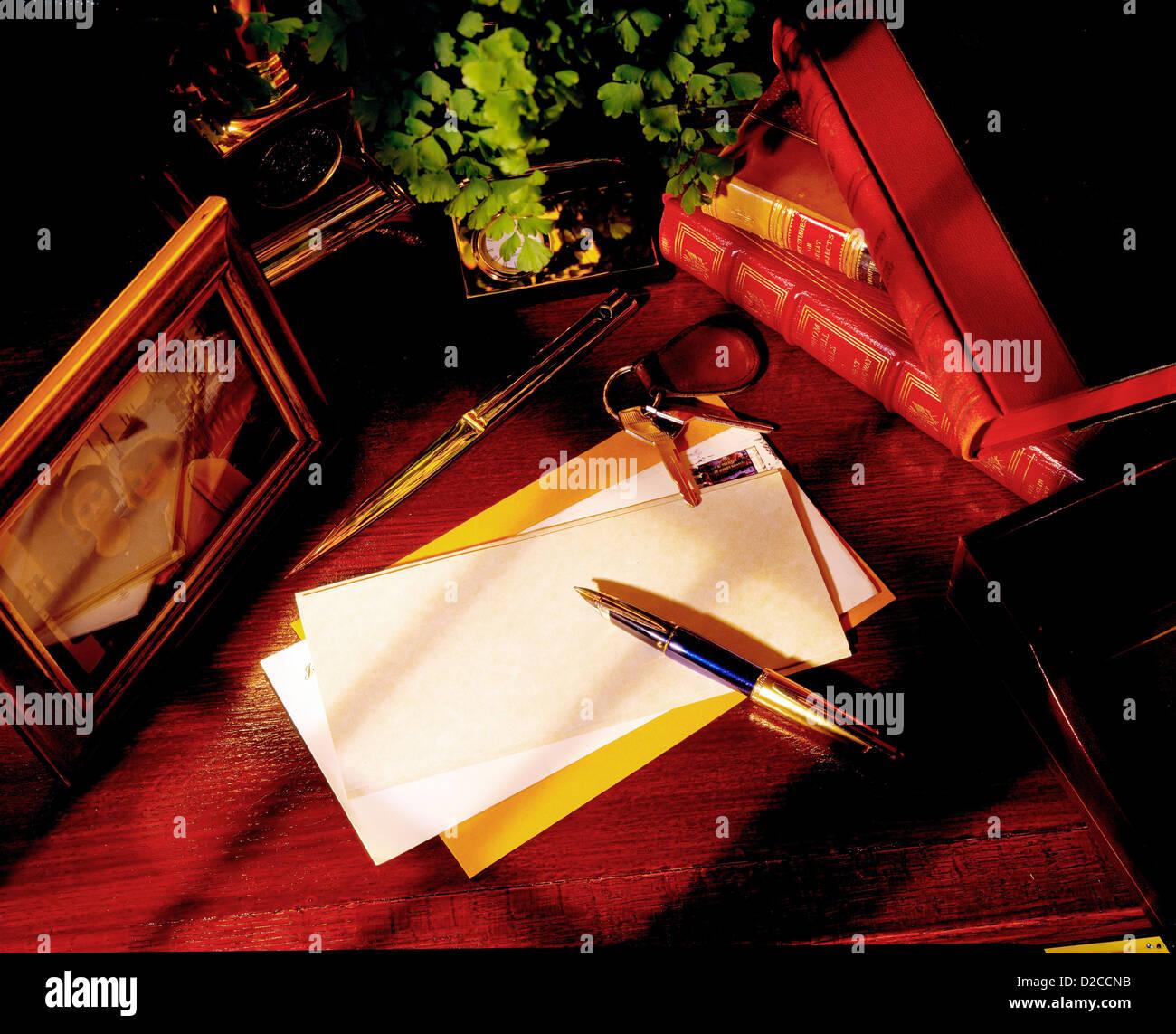 Office Desktop: Bodegón con lápices, papel, correo, llaves, libros y fotografía enmarcada. Imagen De Stock