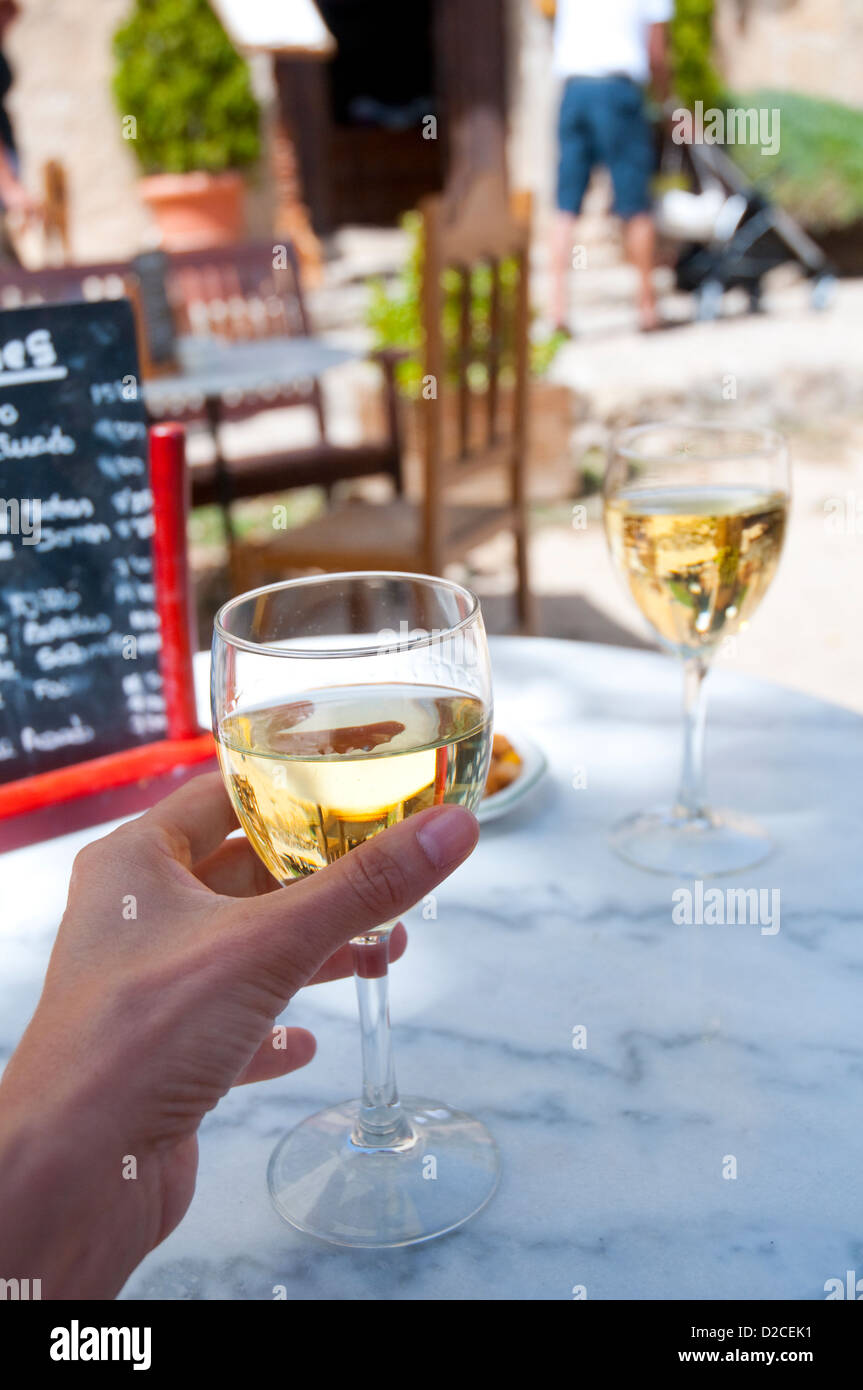 Mano de mujer sosteniendo un vaso de vino blanco en una terraza. Pedraza, provincia de Segovia, Castilla y León, España. Foto de stock