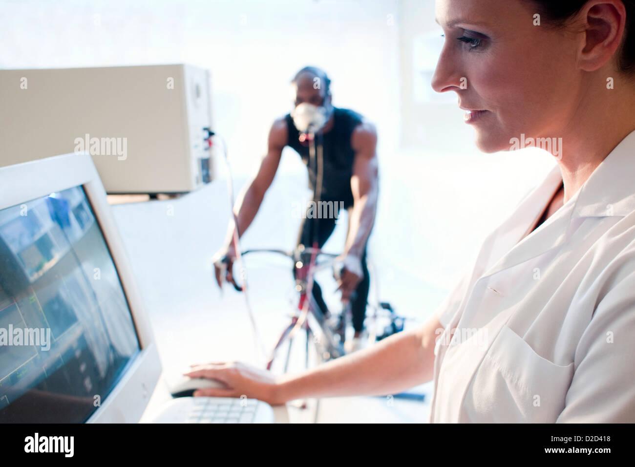 Pruebas de rendimiento liberados modelo deportista montando una bicicleta de ejercicio mientras su rendimiento y Imagen De Stock
