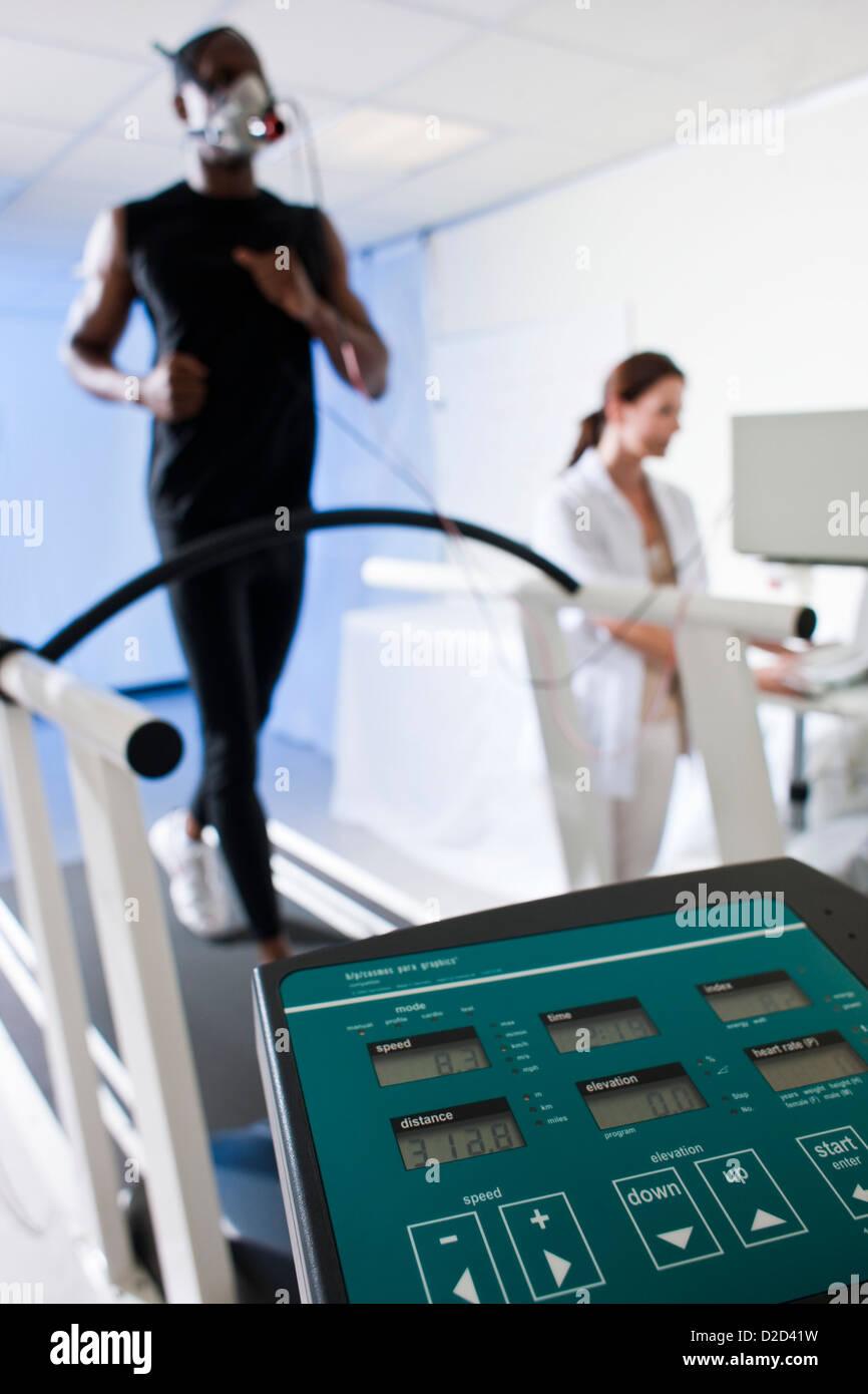 Pruebas de rendimiento liberados modelo atleta corriendo en una cinta andadora su rendimiento y el consumo de oxígeno Imagen De Stock