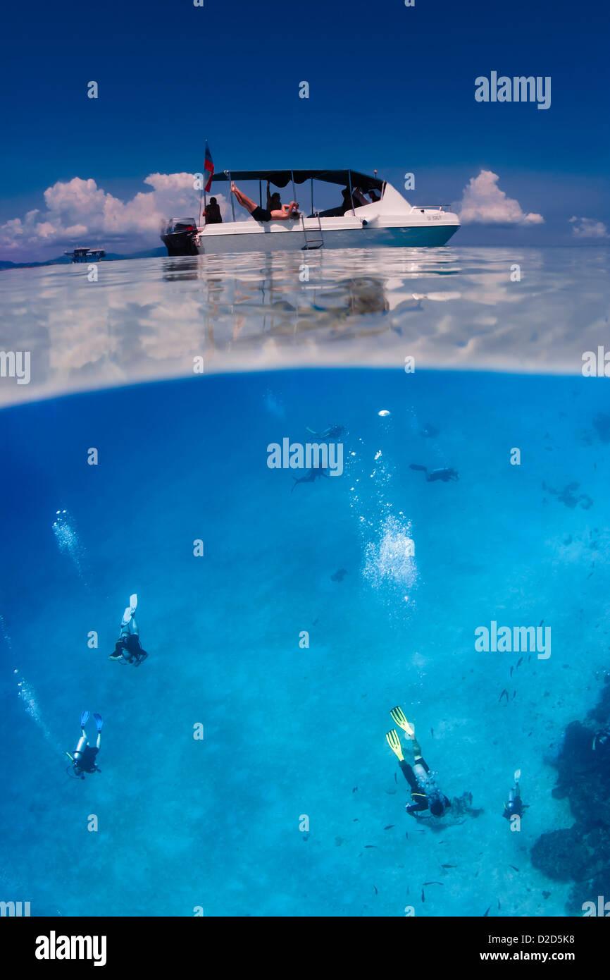 Los buceadores nadando bajo el barco blanco sobre la superficie del océano. División horizontal over/under imagen en color. Foto de stock
