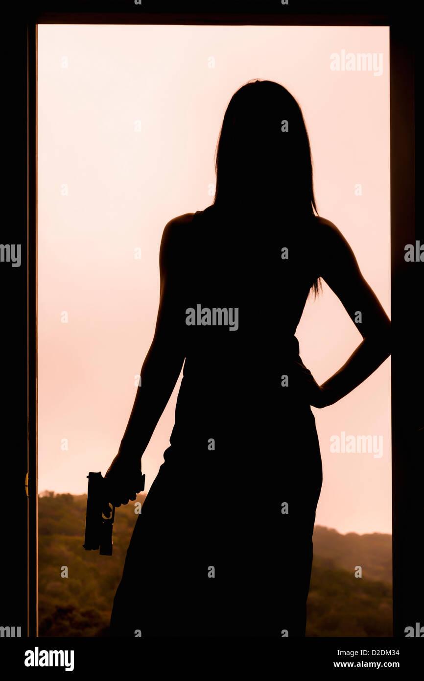 Silueta de una mujer con una pistola mientras está de pie en el marco de una puerta. Imagen De Stock