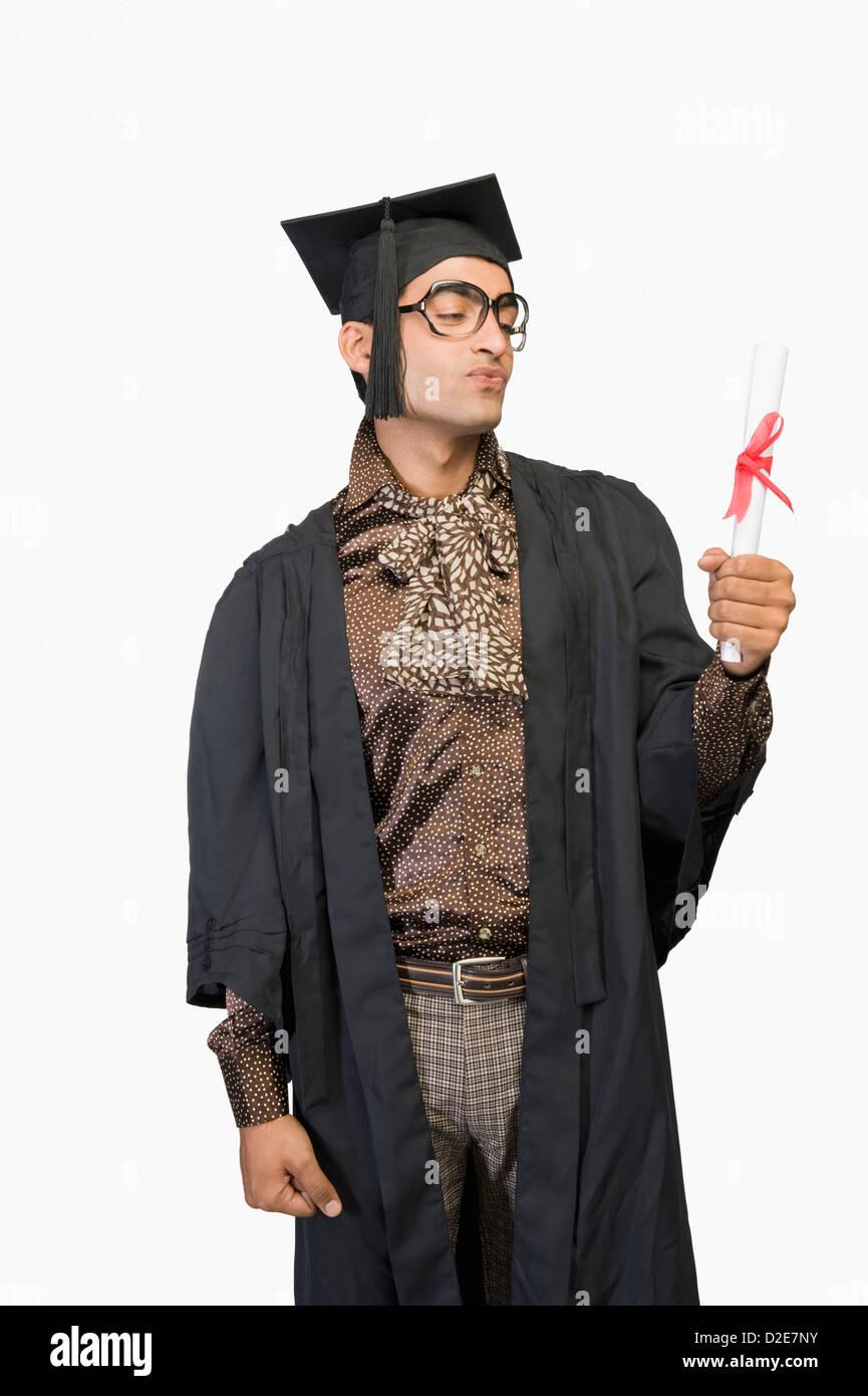 11f4aab85 Hombre en una bata sosteniendo un diploma de graduación Foto ...