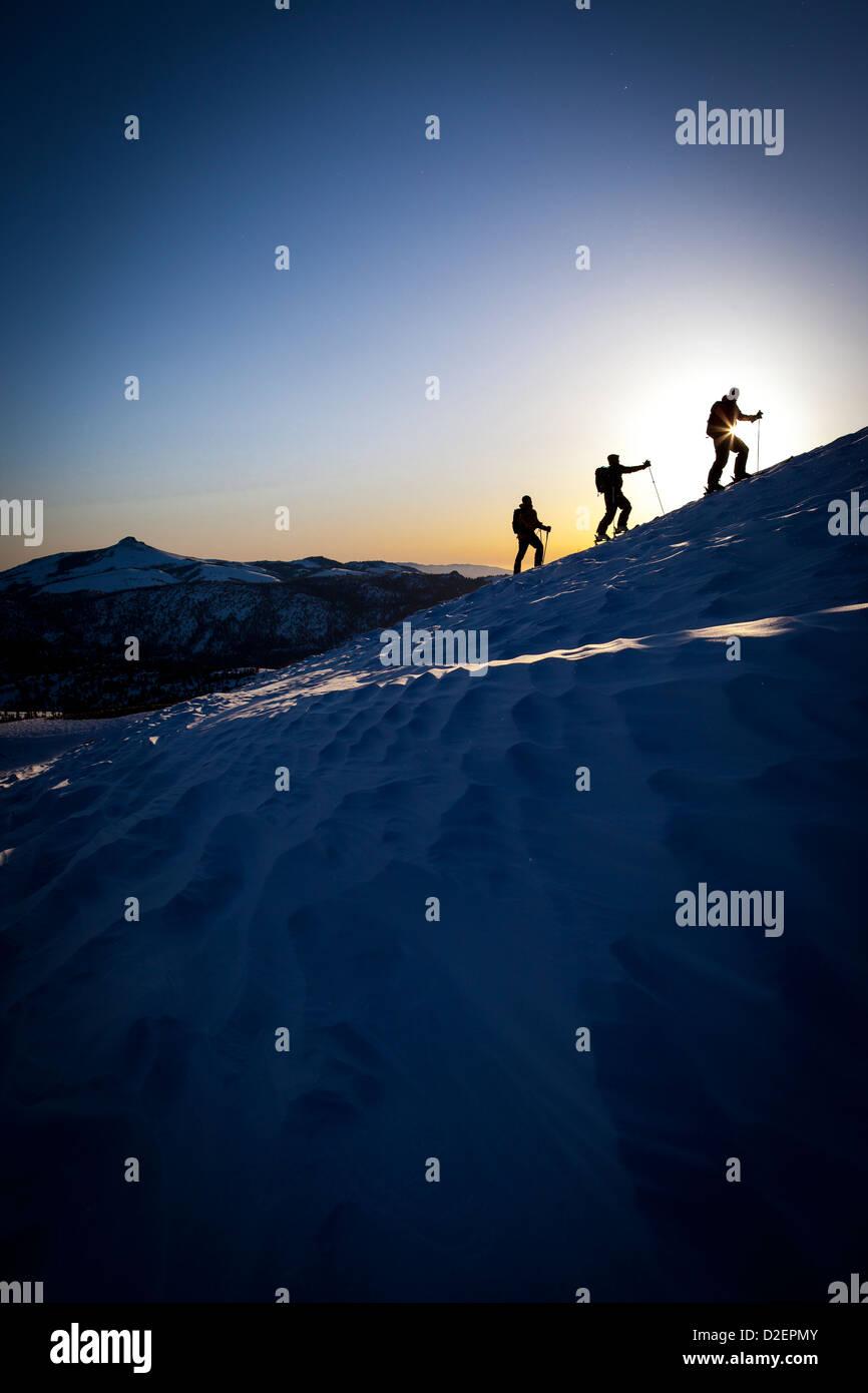 Tres esquiadores de travesía silueteado en la hermosa luz del amanecer. Imagen De Stock